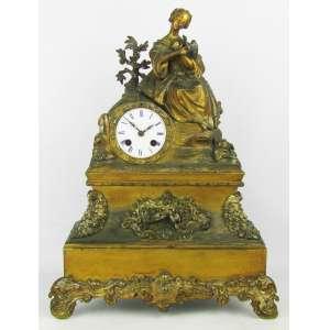 Relógio de mesa europeu, com caixa em bronze e metal dourado, adornado por dama com passaro. Mostrador em porcelana com números romanos. Falta chave e sineta. Maquina não testada. Acompanha pendulo adaptado. Marcas do tempo. Med. 46x34x12,5cm.