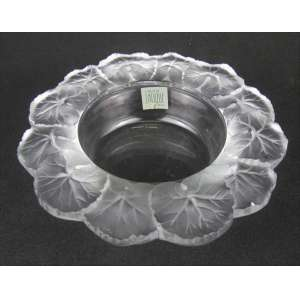 Porta garrafas em cristal francês, com selo da Cristallerie Lalique. Borda com lapidações de folhas em satiné. Fundo translúcido. Pequenos bicados na borda. Med. 6x21,5cm.