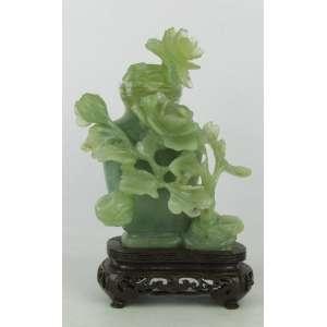 Antigo perfumeiro em jade verde ricamente contornado por galhos florais em relevo, de procedência chinesa, Dinastia Qing - último período imperial (1644-1912). Peça única, similar apregoada na Sotheby's em novembro/2000. Alt. total 18cm.