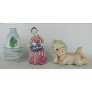 Três peças em porcelana policromada, sendo pequeno vaso alemão, da manufatura Ilmenau, e duas estatuetas, uma representando menina com cesta e a outra bebe em repouso. Alt. vaso 11cm.