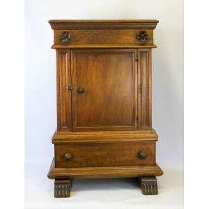 Mesa de apoio em madeira entalhada, com uma gaveta na parte superior, uma na inferior e uma banda de porta central. Med. 75x51x37cm.