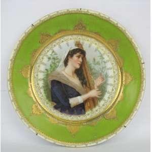 Prato de coleção em porcelana alemã, decorado ao centro com pintura de jovem tocando harpa. Detalhes em dourado. Marca da manufatura Suhl, fundado em 1861. Diam. 24cm.