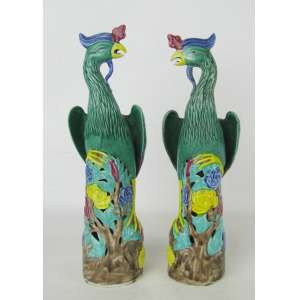 Par de estatuetas em porcelana oriental, policromada, representando Casal de pássaros, sobre coluna vazada e decorada com flores e folhas nos galhos. Alt. 25,5cm.