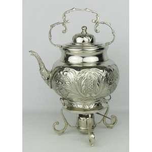 Samovar em metal espessurado a prata, com trabalhos em folhagens e geométricos. Pés em volutas. Alt. 49 cm.