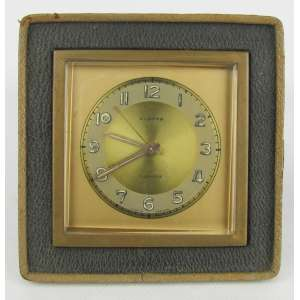 Relógio de coleção para viagem, alemão, marca da manufatura Europa. Caixa com metal dourado. Funcionando. Med. 10,5x10,5 cm.
