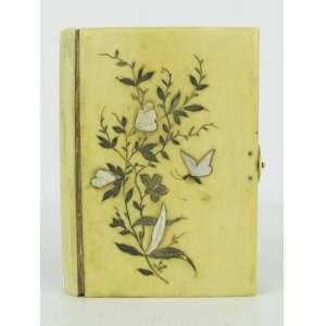 Antigo missal de coleção (Paroissien Romain) com capa em marfim, tendo do lado incrustações em madrepérola na forma de folhagem e flores com borboleta e do outro monograma. Med. 10,5x8 cm.