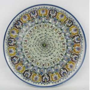 Medalhão em faiança portuguesa Carvalhinho, com pintura de flores e arabescos. Diam. 33 cm.