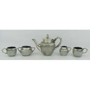Serviço para café em prata alemã contrastada, composto de bule, leiteira, açucareiro e 2 xícaras sem pires. Apresenta pequenas mossas. Peso 365g.Alt. bule 11,5 cm.