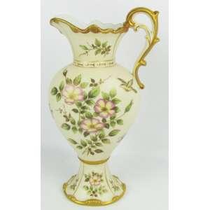 Jarra em porcelana na cor creme, decorada com pintura de animais, flores e folhagens em policromia. Detalhes em dourado. Marca da manufatura na base. Alt. 32 cm.