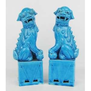Par de estatuetas em porcelana, na cor azul, representando Cães Fó, estando um com seu filhote e um com bola. Alt. 25 cm.