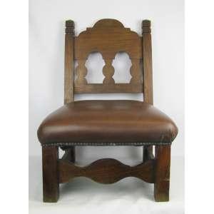 Cadeira para calçar botas, em madeira nobre. Encosto trabalhado com vazados e assento em courvin. Med. 73,5x48x46 cm.