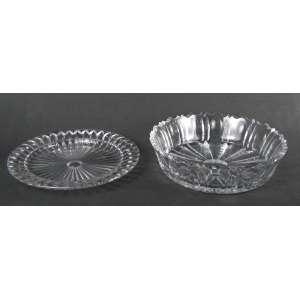 Duas peças em cristal translucido, sendo centro de mesa com lapidações dedão e sulcos, e prato para bolo lapidado em sulcos. Med. centro de mesa 6,5x24,5 e Diam. prato para bolo 24,5cm.