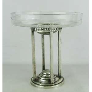 Centro de mesa art-deco, em metal espessurado a prata, formado por 4 colunas de seção quadrada sobre base circular. Prato em demi-cristal translucido, com pequenos bicados. Med. 25,5x24,5 cm.