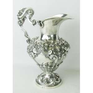 Jarra estilo D. João V, em prata brasileira, teor 800 milésimos, cinzelada em conchas, flores e volutas. Alt. 29cm. Peso 1.100g.