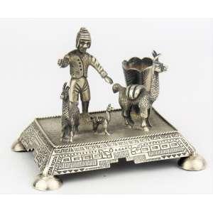 Raro paliteiro em prata peruana martelada, teor 925 milésimos, representando Pastor com lhamas. Marca do contraste, teor e prateiro. Med. 7x8,5x6,5cm.