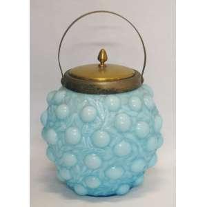 Biscoiteira de coleção em vidro opalinado, na cor azul, decorado com trabalhos de cerejas em relevo. Guarnições em metal. Med. 24x18 cm.