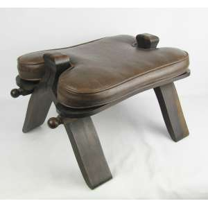 Banco para camelo em madeira nobre entalhada. Acompanha almofada forrada com tecido, imitando couro na cor marrom. Med. 30x52,5x36 cm.
