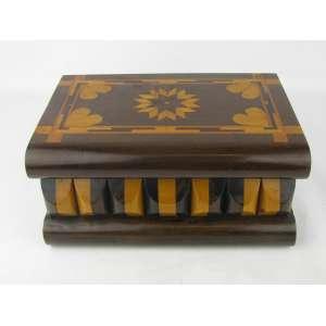 Bela caixa em madeira com trabalhos em marqueterie sobre a tampa. Apresenta compartimento secreto para chave. Necessita pequeno reparo na fechadura. Med. 11,5x23,5x15,5cm.
