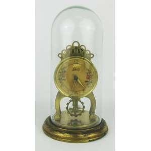 Relógio de mesa alemão com marca da manufatura Schotz. Caixa em bronze e base em metal dourado. Donzela em vidro. Perdas no dourado e maquina necessita reparo. Alt. total 19cm.