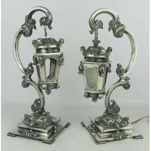 Par de abajours na forma de lanternas em prata portuguesa, contraste Águia, com cinzelados em folhas e volutas. Um não apresenta fiação, sem vidros e lanterna solta. Alt. 32,5cm. Peso 3.000g.