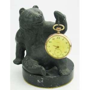 Kramer - Suporte para relógio de bolso em bronze, na forma de urso. Assinado. Base em mármore. Apresenta pequeno bicado na parte de trás do mármore. Acompanha relógio de bolso em plaquet dor, marca Cyma, necessita de reparo. Alt. total da escultura 12,5 cm.