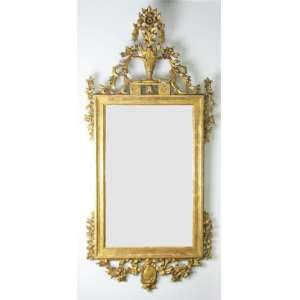 Belo espelho com moldura em madeira dourada e entalhada com flores, folhas, laços de fita, medalhão e perolados. Florão no ápice. Med. 128x58cm.