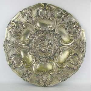 Medalhão estilo D. João V em metal espessurado a prata, com cinzelados de volutas, conchas, folhas e flores em alto relevo. Perdas no prateado. Diam. 46,5cm.