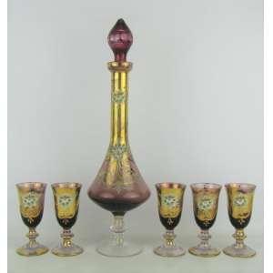 Licoreiro com 5 taças em vidro veneziano na cor vinho, decorado com detalhes em dourado e pintura de flor e folhas em policromia. Com perdas no dourado e tampa do licoreiro com bicados. Alt. licoreiro 39,5cm.