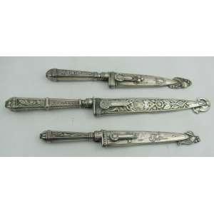Três pequenas facas com bainha de coleção, em metal espessurado a prata, sendo 2 decoradas com cenas de boiadeiros e a outra com flores, folhas e volutas. Comp. maior e menor 23,5x17,5 cm.