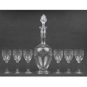 Licoreiro com 6 taças em cristal francês da Cristallerie St Louis, com lapidações em satiné de guirlandas, medalhões e laços de fita. Alt. licoreiro 33,5 cm. Alt. taça 13 cm.