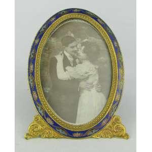 Porta retratos ovalado em metal dourado, com pintura esmaltada na cor azul e detalhes em policromia. Med. 15x10 cm.