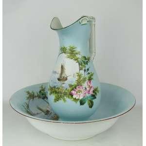 Serviço para toalete em porcelana francesa, Velho Paris, do sec. XIX, na cor azul, com pintura de marinha em reserva, flores e folhagens em policromia, composto de gomil e bacia. Alt. gomil 38 cm. Med. bacia 12x44 cm.