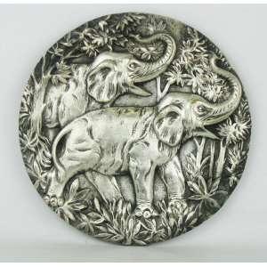 Placa decorativa, circular, em bronze espessurado a prata, tendo ao centro cena com elefantes em relevo. Diam. 22 cm.