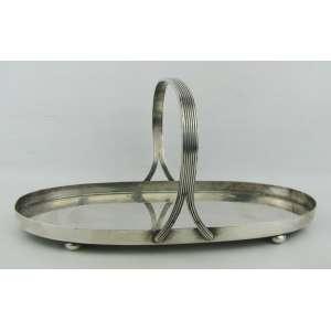 Petisqueira oval com alça, em metal francês espessurado a prata, com marca da manufatura Christofle na base. Alça com trabalhos frisados e pés em bola. Med. 14x29,5x19 cm