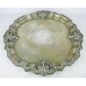 Grande salva em metal espessurado a prata, com trabalhos de flores, folhas, volutas e arabescos em relevo. Diam. 46,5 cm.