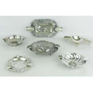 Seis cinzeiros em prata de diversos modelos e decorações, sendo 5 contrastados. Apresentam pequenas marcas do tempo. Med. maior e menor 3,5x18x9 e 10x9,5 cm. Peso 365 gramas.