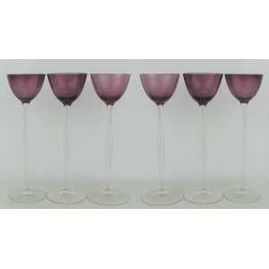 Seis taças de pé alto em cristal na cor vinho, com hastes e bases translúcidas. Alts. 25cm.