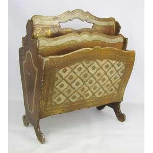 Revisteiro, estilo veneziano em madeira dourada e patinada, na cor creme. Apresenta 4 divisórias. Pés em volutas. Apresenta perdas. Med. 44,5x39x26 cm.