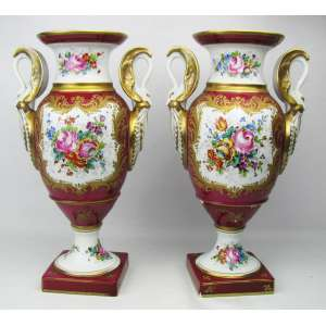 Belo e antigo par de vasos estilo Napoleônicos em porcelana francesa ricamente decorados com flores em policromia e ricos detalhes em ouro brunido. Laterais opostas com figuras de gansos estilizados a guisa de alças. Apresentam bicados. Alt. 39cm.