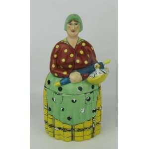Caixa art-deco francesa - Baghavat, em porcelana policromada, na forma de figura com cesta contendo uma ave. Perdas na pintura preta da roupa. Alt. 22 cm.