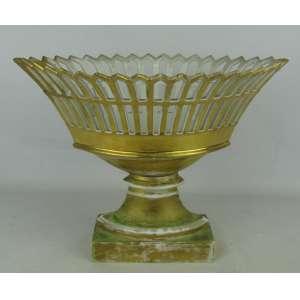 Fruteira em porcelana no tom dourado, com trabalhos vazados na aba. Base retangular. Apresenta restauro e perdas no dourado. Med. 26x34,5x18,5cm.