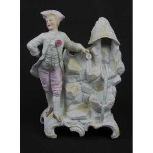 Floreira em biscuit europeu, na forma de fonte, com trabalhos em relevo e adornado com figura de jovem da nobreza. Pés curvos. Med. 19x12x12cm.