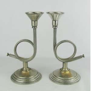 Par de castiçais ingleses, marca da manufatura de Sheffield plate, na forma e cornetas. Apresenta desgaste no prateado. Alt. 25 cm.