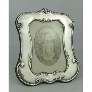 Porta retratos em prata contrastada, com trabalhos em relevo de volutas e folhas. Med. 18,5x16 cm.