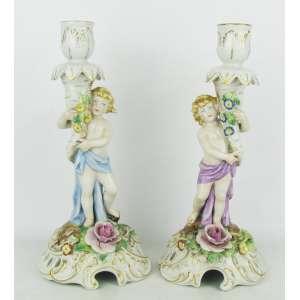 Belo par de castiçais em porcelana alemã, com marca da manufatura na base, na forma de meninos segurando cornucópia. Base decorada com flores, folhas em relevo e vazados. Detalhes em dourado. Pequena quebra em uma flor. Alts. 26 cm.