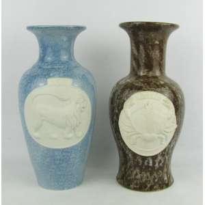 Dois vasos em biscuit esmaltado, sendo um na cor azul decorado com um leão e o outro marrom com um caranguejo em alto relevo, representando os signos de leão e câncer. Alts. 24,5 e 25cm.