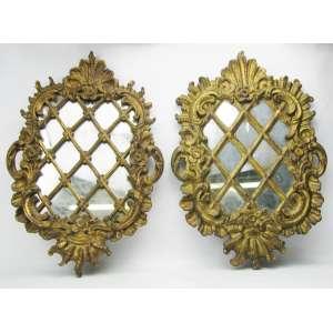 Par de antigas placas, com espelho do Séc. XIX, em madeira dourada e entalhada em flores, folhas e volutas. Espelhos com marcas do tempo. Med. 46x31,5cm.