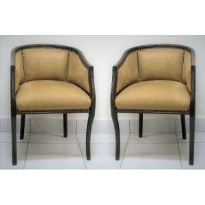 Par de cadeiras de braços em madeira nobre entalhada. Encosto e assento estofado e forrados em tecido no tom bege. Pernas torneadas. Med. 77x54x53cm.