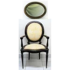 a) Cadeira de braços medalhão em madeira nobre entalhada. Assento e encosto estofados e forrados em tecido. Pernas torneadas afinando para baixo. Med. 01x58x52cm. <br />b) Espelho de parede oval com moldura em madeira entalhada e patinada de dourado. Decorado com folhas e flores em relevo. Med. 44,5x59cm.