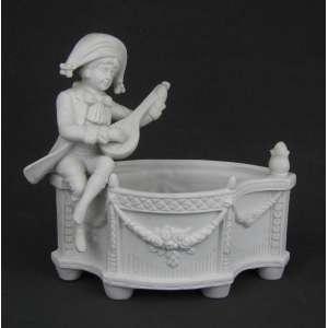 Floreira em biscuit decorada com guirlanda e trabalhos em relevo. Adornada com figura de menino tocando música. Med. 18x20x12 cm.